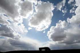 This is picture of a long distance hauling truck with a bright cloud covered skyline.